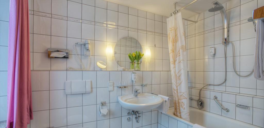 großes Badezimmer mit Badewanne, Regendusche, Fön, Blumendeko