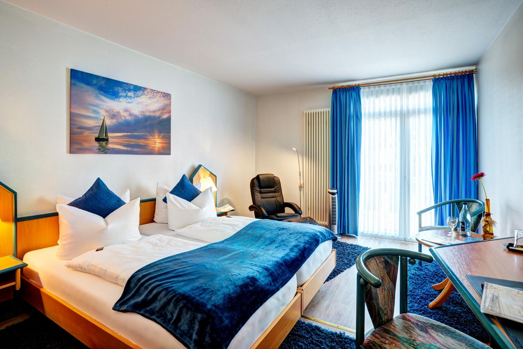 Helles Komfort Doppelzimmer mit Flatscreen und Relaxsessel