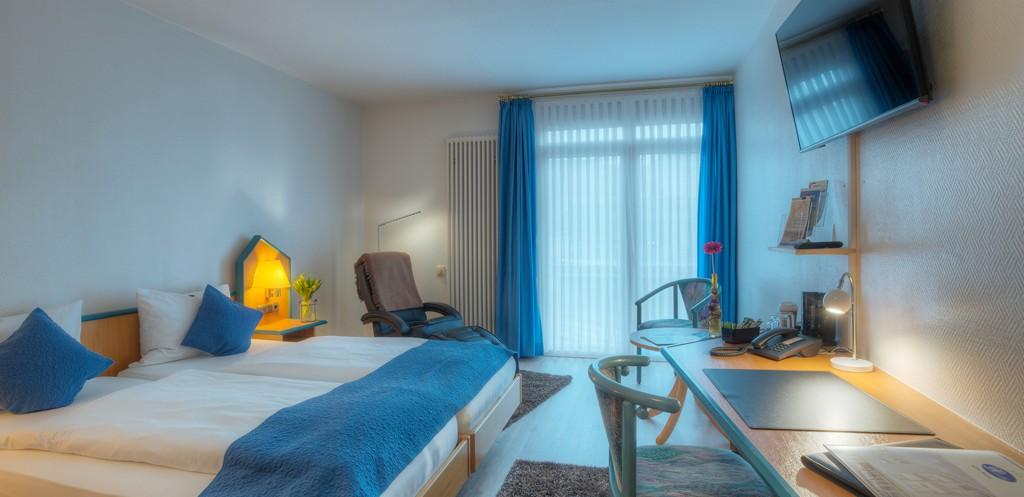 Helles Komfort Doppelzimmer mit Relaxsessel, Flatscreen und Schreibtisch
