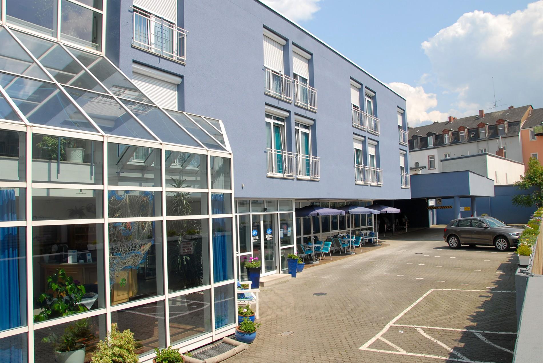 Außenansicht des Hotel Paulin mit Terrasse, Parkplätzen und Einfahrt zur Tiefgarage